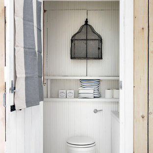 Inspiration for a beach style cloakroom in London with white walls.