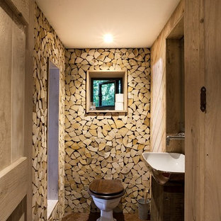 Inspiration for a medium sized rustic cloakroom in Dorset with a one-piece toilet, a vessel sink, brown floors and dark wood cabinets.