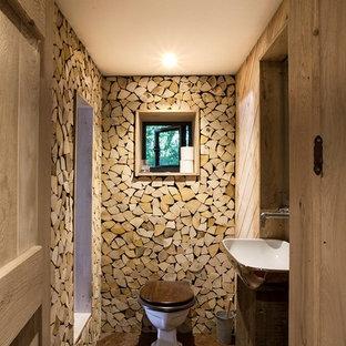 Idée de décoration pour un WC et toilettes chalet de taille moyenne avec un WC à poser, une vasque, un sol marron et des portes de placard en bois sombre.