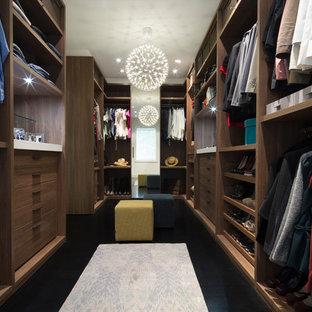 Modern inredning av ett stort omklädningsrum för könsneutrala, med släta luckor, skåp i mellenmörkt trä, mörkt trägolv och svart golv