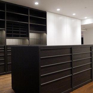Idées déco pour un très grand dressing contemporain avec un placard à porte plane, des portes de placard en bois sombre et un sol en bois brun.