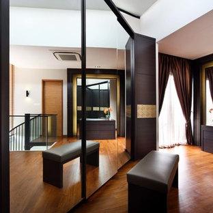 Diseño de vestidor asiático con armarios con paneles lisos y puertas de armario de madera en tonos medios