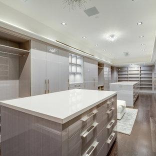 Imagen de armario vestidor de hombre y abovedado, minimalista, extra grande, con armarios con paneles lisos, puertas de armario de madera clara, suelo de madera en tonos medios y suelo marrón