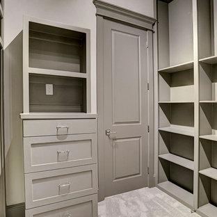 Ejemplo de armario vestidor unisex, de estilo americano, grande, con armarios con puertas mallorquinas, puertas de armario grises, moqueta y suelo beige