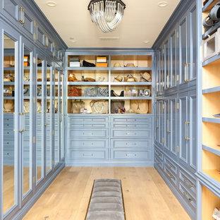 Modelo de vestidor de mujer, clásico renovado, extra grande, con armarios con paneles empotrados, puertas de armario azules, suelo de madera clara y suelo beige