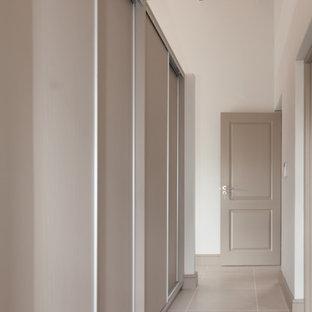 Mittelgroßer, Neutraler Landhaus Begehbarer Kleiderschrank mit flächenbündigen Schrankfronten, beigen Schränken, Porzellan-Bodenfliesen und freigelegten Dachbalken in Sonstige