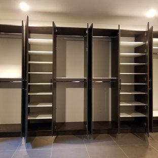 Imagen de vestidor unisex, moderno, extra grande, con armarios con paneles lisos, puertas de armario de madera en tonos medios, suelo de baldosas de porcelana y suelo beige