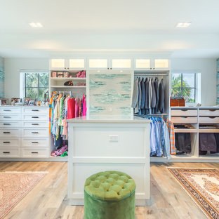 Idéer för ett exotiskt walk-in-closet för könsneutrala, med vita skåp och ljust trägolv