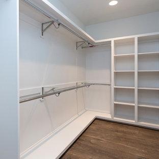 Ejemplo de armario vestidor unisex, minimalista, de tamaño medio, con armarios abiertos, puertas de armario blancas, suelo de madera oscura y suelo marrón