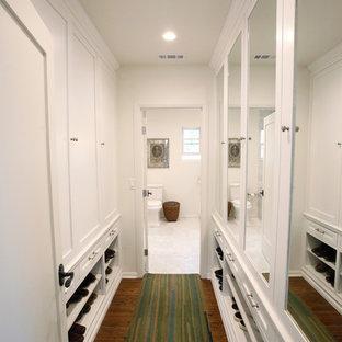 Ispirazione per un armadio o armadio a muro mediterraneo di medie dimensioni con ante con riquadro incassato, ante bianche, pavimento in legno massello medio e pavimento marrone