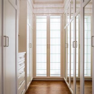 Ejemplo de armario vestidor de mujer, actual, pequeño, con armarios estilo shaker, puertas de armario blancas y suelo de madera en tonos medios