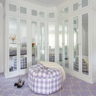 Inredning av ett klassiskt stort omklädningsrum för kvinnor, med luckor med glaspanel, vita skåp, heltäckningsmatta och lila golv