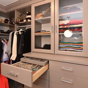 Mid-sized midcentury women's walk-in wardrobe in Houston with glass-front cabinets, beige cabinets, porcelain floors and beige floor.