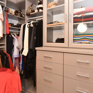 Design ideas for a mid-sized midcentury women's walk-in wardrobe in Houston with glass-front cabinets, beige cabinets and beige floor.