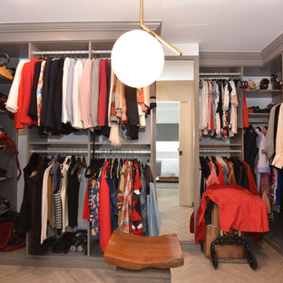 Photo of a mid-sized midcentury women's walk-in wardrobe in Houston with glass-front cabinets, beige cabinets, porcelain floors and beige floor.