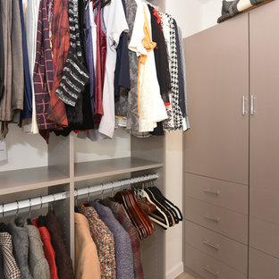 Diseño de armario vestidor de mujer, vintage, de tamaño medio, con armarios tipo vitrina, puertas de armario beige, suelo de baldosas de porcelana y suelo beige