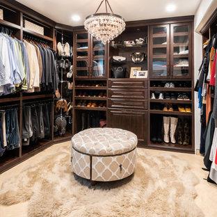 Immagine di una cabina armadio unisex di medie dimensioni con ante con bugna sagomata, ante in legno bruno, pavimento con piastrelle in ceramica e pavimento beige