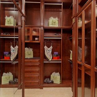 Imagen de armario vestidor unisex, mediterráneo, grande, con armarios con paneles con relieve, puertas de armario de madera oscura y suelo de baldosas de cerámica
