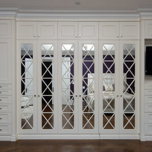 Foto de vestidor de mujer, tradicional renovado, de tamaño medio, con armarios tipo vitrina, puertas de armario blancas y suelo de madera oscura