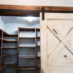 Immagine di una cabina armadio unisex rustica di medie dimensioni con nessun'anta, ante in legno bruno e parquet scuro