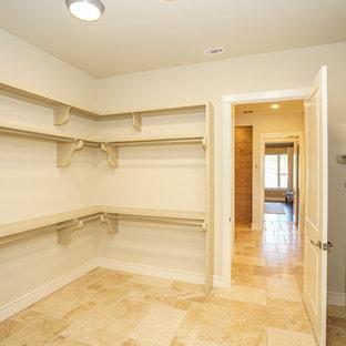 Modelo de armario vestidor unisex, de estilo de casa de campo, de tamaño medio, con armarios con paneles con relieve, puertas de armario beige, suelo de travertino y suelo beige