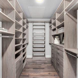 Modelo de armario vestidor unisex, contemporáneo, grande, con armarios abiertos, puertas de armario de madera clara, suelo de madera en tonos medios y suelo marrón