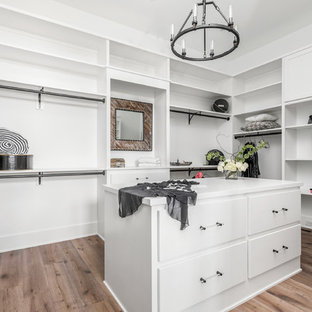 Inspiration for a large country gender-neutral walk-in wardrobe in Indianapolis with flat-panel cabinets, white cabinets, light hardwood floors and multi-coloured floor.