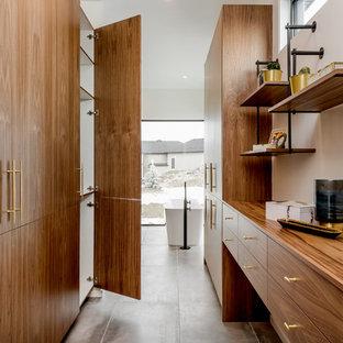 Ejemplo de armario vestidor unisex, retro, grande, con armarios con paneles lisos, puertas de armario de madera oscura, suelo de baldosas de cerámica y suelo gris