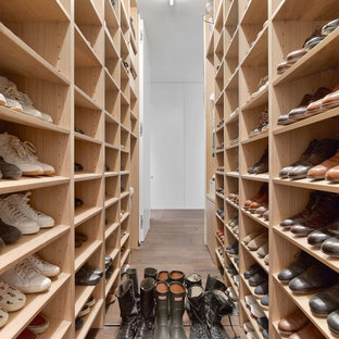Inspiration for a modern men's dark wood floor and brown floor walk-in closet remodel in New York with open cabinets and light wood cabinets