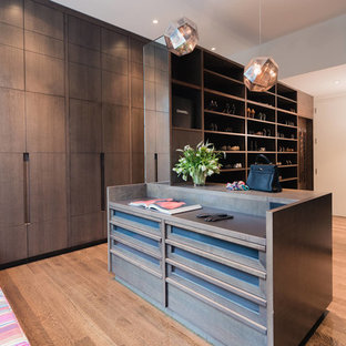 Large trendy gender-neutral brown floor and medium tone wood floor dressing room photo in New York with flat-panel cabinets and dark wood cabinets