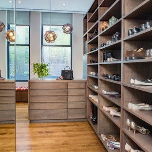 Ejemplo de vestidor unisex, contemporáneo, grande, con armarios con paneles lisos, puertas de armario de madera oscura, suelo de madera oscura y suelo marrón