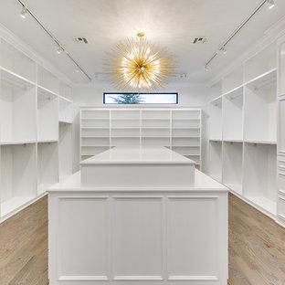Immagine di un'ampia cabina armadio unisex minimalista con ante in stile shaker, ante bianche e pavimento in legno massello medio