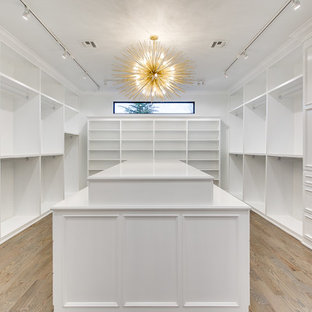 Ejemplo de armario vestidor unisex, minimalista, extra grande, con armarios estilo shaker, puertas de armario blancas y suelo de madera en tonos medios