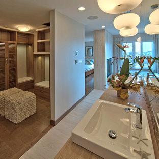 Modern inredning av ett stort walk-in-closet för könsneutrala, med mellanmörkt trägolv, luckor med lamellpanel, skåp i mellenmörkt trä och brunt golv