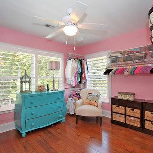 Immagine di un ampio spazio per vestirsi per donna classico con pavimento in legno massello medio