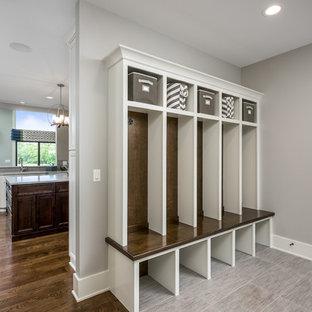 Foto de vestidor unisex, actual, grande, con armarios con paneles con relieve, puertas de armario blancas, suelo de baldosas de cerámica y suelo beige