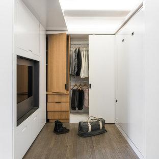 Foto de vestidor unisex, minimalista, pequeño, con armarios con paneles lisos, puertas de armario de madera clara y suelo de madera en tonos medios