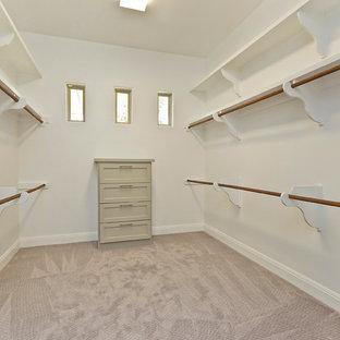 Idée de décoration pour un dressing room tradition de taille moyenne et neutre avec un placard à porte shaker, des portes de placard beiges et moquette.