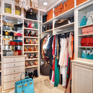 Inspiration for a large mediterranean women's terra-cotta floor walk-in closet remodel in Orange County with beige cabinets and open cabinets