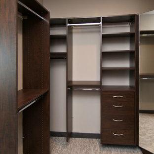 Idee per una cabina armadio industriale di medie dimensioni con nessun'anta, ante in legno bruno e moquette