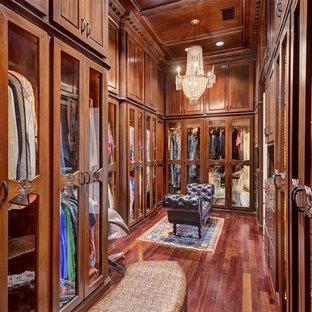 Modelo de armario vestidor unisex, clásico, grande, con armarios tipo vitrina, puertas de armario de madera oscura, suelo de madera en tonos medios y suelo marrón