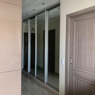 中くらいの男女兼用おしゃれな収納・クローゼット (ガラス扉のキャビネット、グレーの床、格子天井) の写真