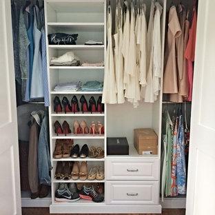 Modelo de armario de mujer, tradicional, pequeño, con armarios con paneles con relieve, puertas de armario blancas, suelo de madera en tonos medios y suelo marrón