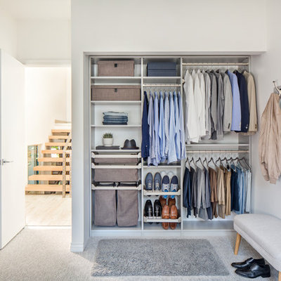 Small elegant men's carpeted and gray floor reach-in closet photo with open cabinets and dark wood cabinets