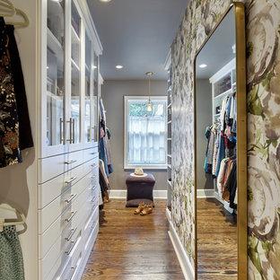 Ispirazione per una cabina armadio per donna chic di medie dimensioni con ante di vetro, ante bianche, pavimento in legno massello medio e pavimento marrone