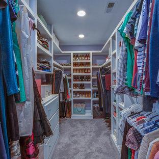 Aménagement d'un dressing classique de taille moyenne avec des portes de placard blanches et moquette.