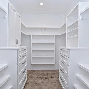 Diseño de armario vestidor clásico renovado, grande, con armarios abiertos, puertas de armario blancas, suelo de cemento y suelo marrón