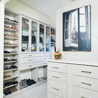 Imagen de armario vestidor retro, grande, con armarios tipo vitrina, puertas de armario de madera clara, moqueta y suelo gris