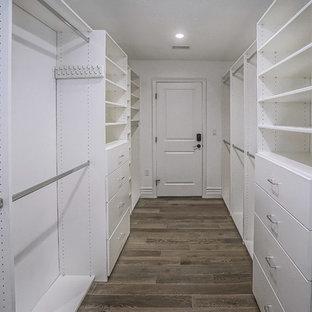 Ejemplo de armario vestidor unisex, retro, de tamaño medio, con armarios con paneles lisos, puertas de armario blancas, suelo de madera oscura y suelo marrón
