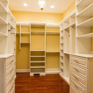 Modelo de armario vestidor unisex, tradicional, grande, con puertas de armario blancas y suelo de madera oscura
